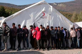 Migrants wait in line to receive supplies from the Red Cross at the Vucjak refugee camp, outside Bihac, in northwestern Bosnia, Oct. 21, 2019.