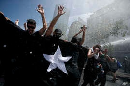 Anti-government demonstrators brace against the force of a police water canon during a general strike in Santiago, Chile, Oct. 23, 2019.