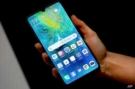 FILE - A staff member holds a Huawei 'Mate20 X 5G' smartphone at the IFA 2019 tech fair in Berlin, Germany, Sept. 5, 2019.