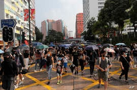 Demonstrators wearing face masks walk down a street during a protest in Hong Kong, Oct. 12, 2019.