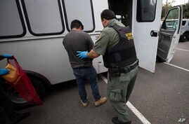 FILE - An U.S. Immigration and Customs Enforcement (ICE) officer transfers a man in hand and ankle cuffs onto a van during an operation in Escondido, California, July 8, 2019.