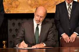 Pennsylvania Gov. Tom Wolf signs an executive order for his administration to start working on regulations to bring Pennsylvania into a nine-state consortium that sets a price and limits on greenhouse gas emissions from power plants, Oct. 3, 2019.
