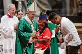 Indigenous peoples, some with their faces painted and wearing feathered headdresses, stand by  Pope Francis as he celebrates an opening Mass for the Amazon synod, in St. Peter's Basilica, at the Vatican, Sunday, Oct. 6, 2019.