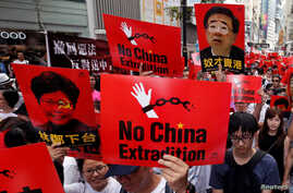 FILE - Demonstrators hold signs protesting an extradition bill during a rally in Hong Kong, June 9, 2019.