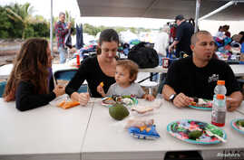 FILE - Members of a family with two children eat a meal in Pahoa, Hawaii, May 7, 2018.