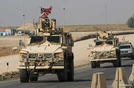 FILE - A convoy of U.S. military vehicles is seen at the Iraqi-Syrian border crossing, on the outskirts of Dohuk, Iraq, Oct. 21, 2019.