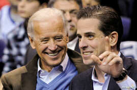FILE - Then-U.S. Vice President Joe Biden and his son Hunter Biden attend an NCAA basketball game between Georgetown University and Duke University in Washington, Jan. 30, 2010.