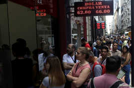 People line up outside a currency exchange store in Buenos Aires' financial district, in Argentina, Oct. 25, 2019.