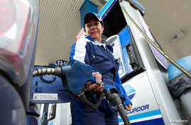FILE - A woman fills a car with fuel at a gas station in Quito, Ecuador, June 1, 2016.