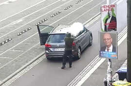 A man shoots a firearm from behind a grey car in Halle, Germany, in this amateur video still image.