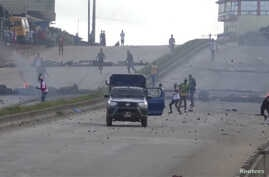 Protesters throw stones at a riot police vehicle on a main road in Sonfonia District in Conakry, Guinea, Oct. 14, 2019, in this still image taken from video.
