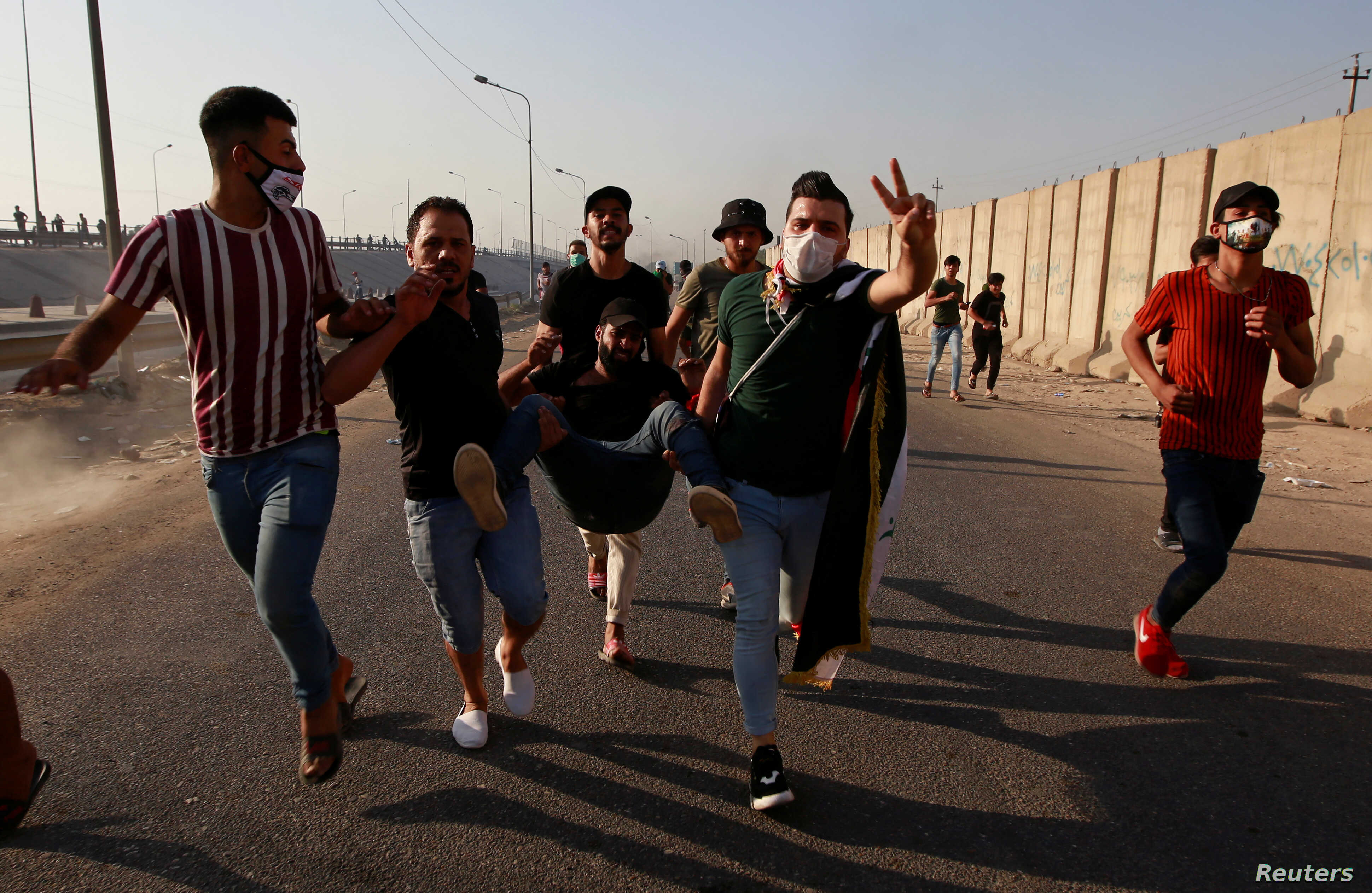 Men carry an injured demonstrator during a nationwide anti-government protests in Baghdad, Iraq, Oct. 3, 2019.