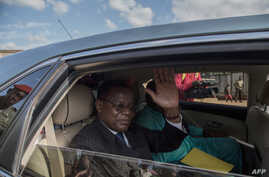 Cameroonian opposition leader Maurice Kamto (L) sits in the back of a car as he is driven away on October 5, 2019, the day of…