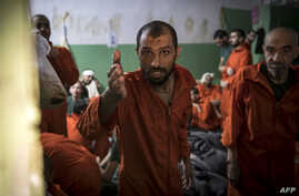Men, suspected of being affiliated with the Islamic State (IS) group, gather in a prison cell in the northeastern Syrian city…