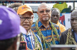 Bougainville regional president John Momis (L) speaks to the media before casting his ballot in an historical independence vote…