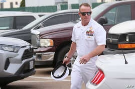 (FILES) In this file photo taken on June 21, 2019 Navy Special Operations Chief Edward Gallagher walks into military court in…
