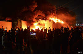 Iraqi demonstrators gather as flames start consuming Iran's consulate in the southern Iraqi Shiite holy city of Najaf on…
