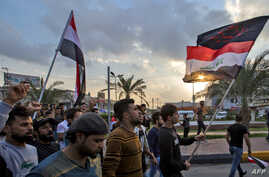 "Iraqi protesters march with national flags and a Shiite Muslim flag reading in Arabic ""oh martyr Hussein"" during an anti…"