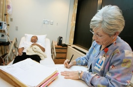 Susan Deautremont, R.N., right, charts information while caring for Sherry Webb, left, at the Sickle Cell Center in Truman…