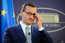 Polish Prime Minister Mateusz Morawiecki adjusts his glasses during joint press statements with Romanian counterpart Viorica…