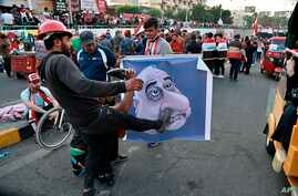Protesters hit a poster showing Iraqi Prime Minister Adel Abdel-Mahdi with shoes during ongoing anti-government protests in Baghdad, Iraq, Nov. 3, 2019.