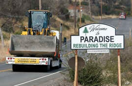 "Vehicles pass a sign welcoming people to Paradise, Calif., Tuesday Nov. 5, 2019. The sign also displays the slogan, ""Rebuilding…"