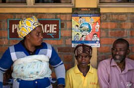 Patients waiting for prescriptions to be filled by the hospital pharmacy sit underneath a sign warning about the symptoms of Ebola, at Kibogora district hospital, near Lake Kivu and close to the border with Congo, in western Rwanda, Nov. 4, 2019.