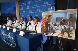 A photo of a patient being transported is displayed while medical staff at Henry Ford Hospital answer questions during a news…