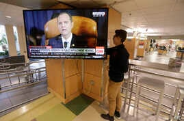 University of Utah student Suyog Shrestha turns on a TV in the student union on the campus in Salt Lake City as Rep. Adam Schiff, the Democratic chairman of the House Intelligence Committee, makes his opening remarks, Nov. 13, 2019.