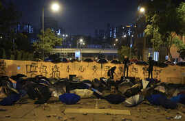 Pro-democracy protesters barricade a road scattered with umbrellas and bricks outside the campus of the Hong Kong Baptist…