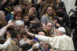 Pope Francis salutes faithful in the Paul VI Hall at the Vatican at the end of an audience with members of parish…