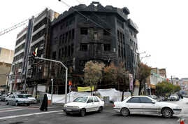Traffic passes a building that was set ablaze during recent protests over government-set gasoline prices rises, in Tehran, Iran…