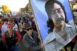 FILE - Marchers carry a large painting of jailed American Indian Leonard Peltier during a march for the National Day of Mourning in Plymouth, Mass, Nov. 22, 2001. United American Indians of New England held its first National Day of Mourning in 1970.