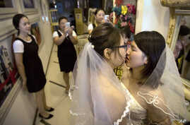 FILE - In this July 2, 2015, file photo, Teresa Xu, left, and Li Tingting, right, share a kiss as clerks take photographs in a…