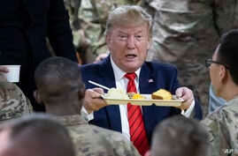 President Donald Trump holds up a tray of Thanksgiving dinner during a surprise Thanksgiving Day visit to the troops,Nov. 28, 2019, at Bagram Air Field, Afghanistan.