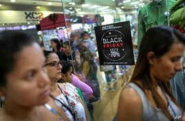 Shoppers walk past a sign promoting Black Friday sales at the Sambil shopping center in Caracas, Venezuela, Nov. 29, 2019.