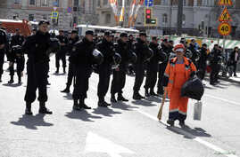 FILE - A sweeper walks past police officers as they stand guard during a rally of Russian opposition supporters in Moscow, May 6