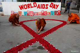Buddhist monks light candles during an HIV/AIDS awareness campaign on the occasion of World AIDS Day in Kolkata, India,…