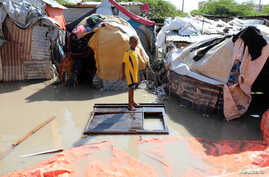 A Somali boy stands on a wooden cupboard after heavy rain flooded their neighbourhood in Mogadishu, Somalia October 21, 2019…