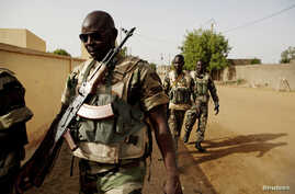 Soldiers from the Waraba Battalion, an EU-trained Malian army battalion, walk outside their base in Gao July 8, 2013. Picture…