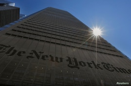 The sun peaks over the New York Times Building in New York August 14, 2013. People accessing nytimes.com earlier on Wednesday…