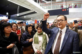 Cambodia's self-exiled opposition party founder Sam Rainsy, who has vowed to return to his home country, gestures to supporters…