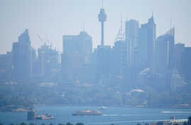 A ferry passes in front of the Central Business District as smoke from bushfires shroud Sydney, Australia, November 11, 2019.  …