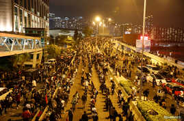 Anti-government demonstrators block a road near the Hong Kong Polytechnic University (PolyU) in Hong Kong, China November 18,…