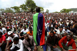 FILE PHOTO: A Sidama youth leader carrying a flag addresses people as they gather for a meeting to declare their own region in…