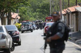 FILE PHOTO: A police officer is seen near a site where an armed gang holds people hostage after they robbed a securities…