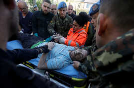 Military and emergency personnel helps an injured man in Thumane, after an earthquake shook Albania, Nov. 26, 2019.