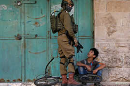 An Israeli soldier detains a Palestinian boy during an anti-Israel protest in Hebron in the Israeli-occupied West Bank November…