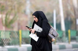 A woman uses a smartphone while standing alongside a street in the Iranian capital Tehran, Nov 23, 2019.