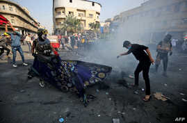 Iraqi demonstrators grapple with a tear gas canister during clashes with security forces in the capital Baghdad's al-Rasheed street near al-Ahrar bridge, Nov. 26, 2019.